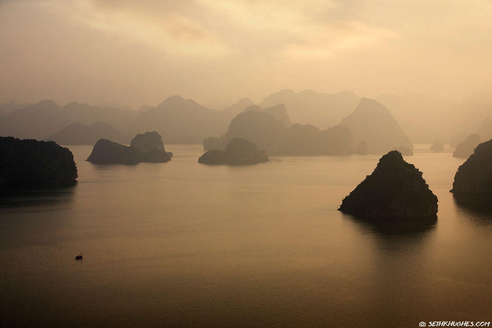Ha Long Bay, located in the Quảng Ninh province of Vietnam, is a UNESCO World Heritage site. A fisherman navigates the waters at sunset as several limestone islets fade into the distance. May 5, 2008