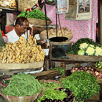 Ginger, Cauliflower and Mixed Green Vegetables Stall at Street Market in Mumbai, India<br /> Vegetables in Mumbai, India, are frequently sold in closet-sized stalls that line a street market.  This vendor of ginger, cauliflower and mixed green vegetables tried to beautify his stall with shelf-lining-paper tacked along the walls.