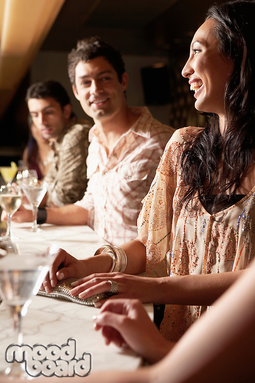 Mid-adult People standing at Bar with cocktail glasses socializing