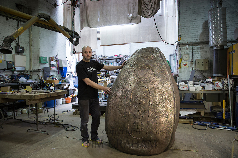 Gavin Turk, artist, photographed at a foundry in East London with his bronze rubgy ball sculpture destined for installation at Rugby School - the birthplace of rugby ----------COPYRIGHT - TIM GRAHAM. For permission to use  this image please contact mail@timgraham.co.uk