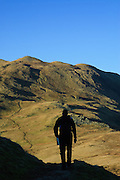 A walker silhoutted with Place Fell, and Boredale Hause, beyond, in Patterdale, Ullswater, Lake District, Cumbria