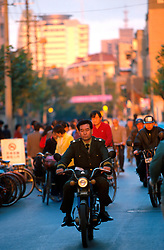 CHINA SHANGHAI NOV01 - A uniformed motorcyclist goes through the downtown traffic.. . . jre/Photo by Jiri Rezac. . © Jiri Rezac 2001. . Contact: +44 (0) 7050 110 417. Mobile:  +44 (0) 7801 337 683. Office:  +44 (0) 20 8968 9635. . Email:   jiri@jirirezac.com. Web:     www.jirirezac.com