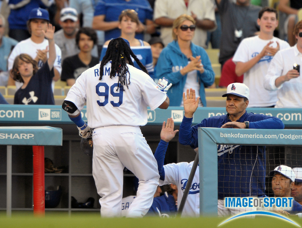 May 31, 2010; Los Angeles, CA, USA; Los Angeles Dodgers left fielder Manny Ramirez (99) is greeted by manager Joe Torre (6) after hitting a solo home run in the second inning of the game against the Arizona Diamondbacks at Dodger Stadium.