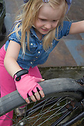 Polish girl age 4 preparing to ride bike wearing pink fingerless bicycle gloves. Zawady Central Poland