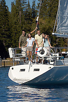 Friends Standing on Stern of Sailboat