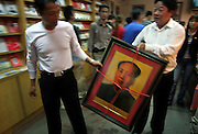 SHAOSHAN, CHINA - 4 NOVEMBER 2005 - Tourists walk away with a framed portrait of Mao at the Mao Family Temple in Shaoshan. Shaoshan has become a money spinning attraction that symbolizes one of the great contradictions of the politics of the ruling Communist Party of China. Photo by Natalie Behring