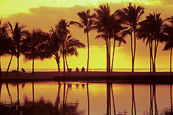 United States, Hawaii, Big Island, couple, palm trees and sunset reflected in a lagoon at 'Anaeho'omalu Bay