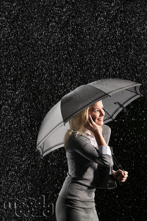 Businesswoman standing under umbrella talking on mobile