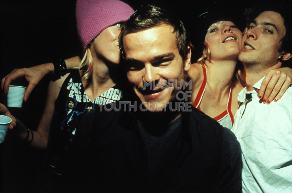A man in dark clothing and smart hair, another wearing magenta coloured hat and two more hugging, Le Batoter Paris, France, 1999.