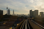 Entering the Malaysian city of Kuala Lumpur by train at dawn