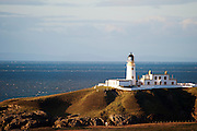 Lighthouse on hill with sea and blue sky in the background, Souther Upland Way, Portpatrick