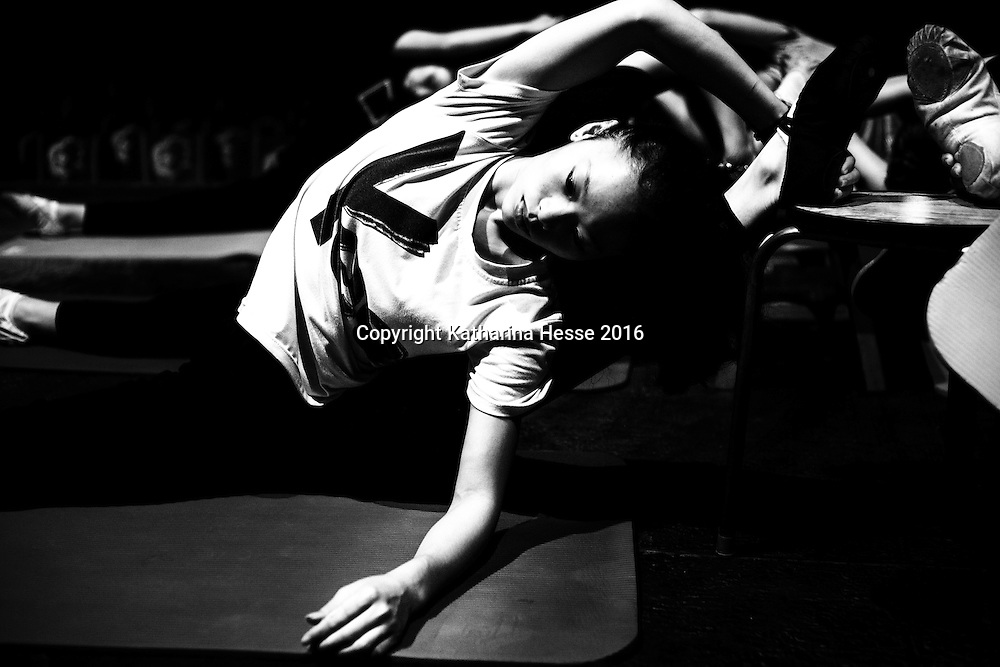 Beijing, Aug.1, 2016 : a young performer stretches during rehearsals for a show.<br /> Acrobatic performances belong to Chinas variety arts and have existed for centuries. Acrobats originally were to entertain poor villagers in the countryside. Nowadays it's a profession for young people from the countryside seeking a better life in China's big cities where they lead a life as outcasts. Their monthly income is not enough to participate in social life , let alone to have private lifes. The troupes often live together in basic housing such as dorms and it's difficult to break out.