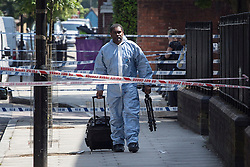 © licensed to London News Pictures. London, UK 27/07/2013. Forensic officers investigating a scene where a man was found stabbed in Poplar, east London.The victim, believed to be aged in his early 30s,  was announced dead on Friday, July 26 night. The Metropolitan Police said two men have been arrested on suspicion of murder following the investigation. Photo credit: Tolga Akmen/LNP