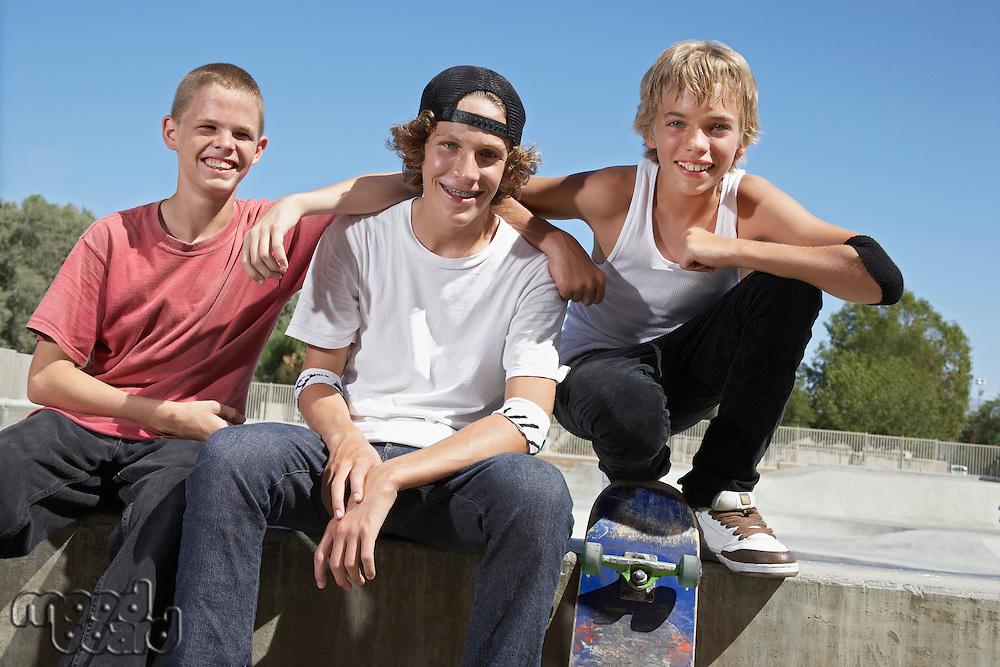 Three teenage boys (16-17) with skateboards at skate park portrait