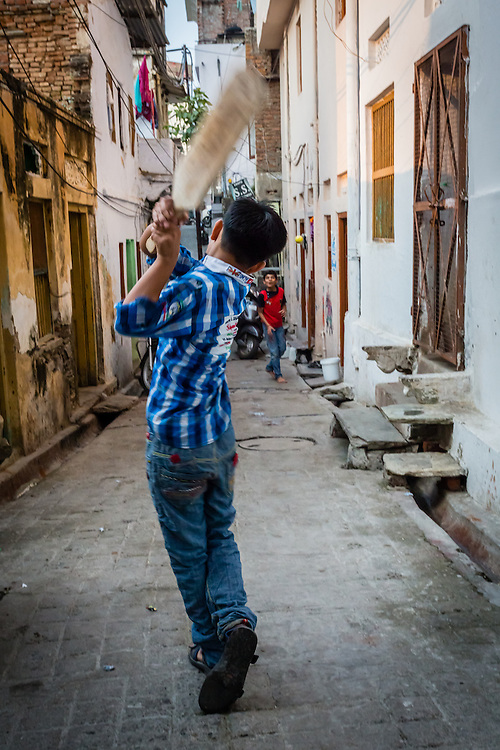 A kid playing cricket in a street in Udaipur. Cricket in India, as in most former british colonies, is the number one sport, and cricket players are considered almost gods.