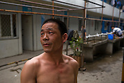Huang Neng, a welder from Henan Province stands outside one of the workers' quarters near a construction site in the Pudong area of Shanghai, China. (He is featured in the book What I Eat: Around the World in 80 Diets). The caloric value of his day's worth of food on a typical day in June was 4300 kcals. He is 36 years old; 5 feet, 6 inches tall and 136 pounds. The migrant welder has worked on a dozen trophy skyscrapers on the Huangpu River in Pudong New Area, across the river from old Shanghai. His current project is the Zhongrong Jasper Tower, which will top out at 48 floors, a short-statured building compared to its neighbors. MODEL RELEASED.