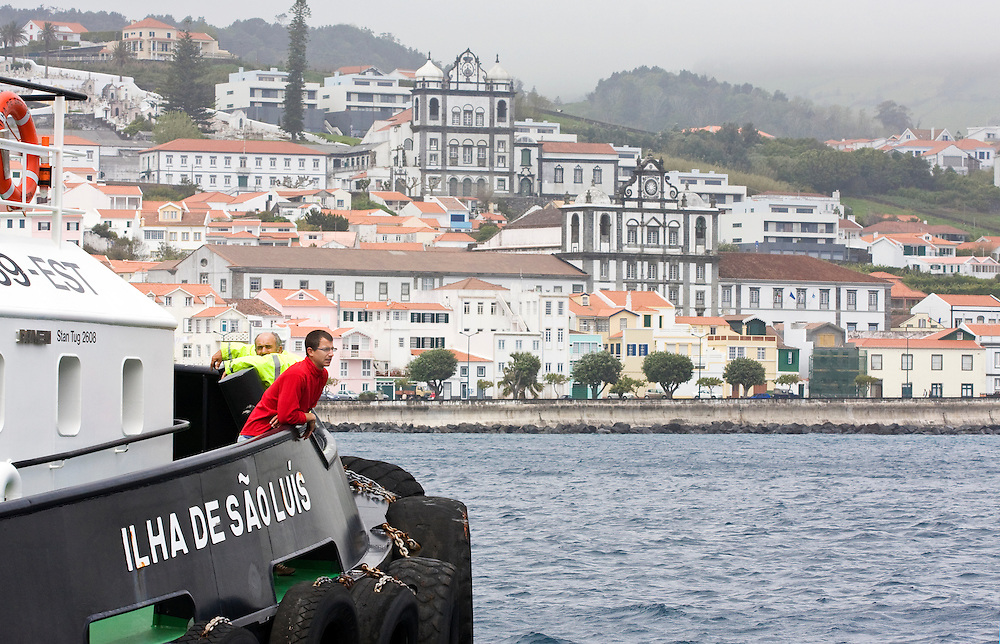 The crew of a tug boat talk to officials on the dock before leaving Horta's commercial harbor to assist a cruise ship due to arrive which is expericencing engine trouble..Horta is on the Portuguese island of Faial, one of the Azores, which mark the most western boundaries of the E.U.