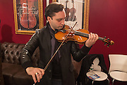 A visitor tries a violin by Florian Leonhard Fine Violins of London.