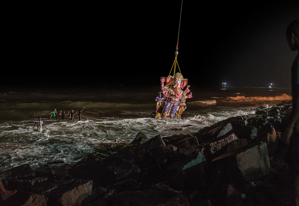 Young men guide a massive papier-mâché statue of Lord Ganesh by rope as it is immersed in the surf by a crane for the Ganesh Chaturthi Festival so it can symbolically go back to nature.