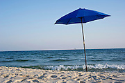 A single blue umbrella sits on the beach.