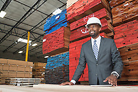 An African American male contractor standing in front of stacked wooden planks