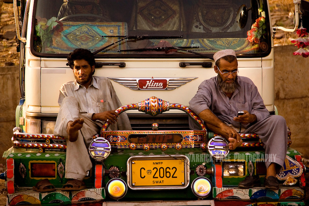 RAWALPINDI, PAKISTAN - OCTOBER 9: Pakistani mechanics rest after completing repairs at a painting and repair yard, October 9, 2008, in Rawalpindi, Pakistan. The heavily adorned Bedford trucks have become a national icon and cost upwards of one million rupees (USD$12,500) for a full makeover. Much of the artwork consists of a cultural mix of religious and secular, Pakistani film and music stars, cricket legends, romanticized military imagery of F-16 fighter jets and Ghauri missiles, the Prophet's winged horse, Buraq, and dreamlike scenes of wooded lakes and snow-capped mountains and exotic animals. (Photo by Warrick Page)