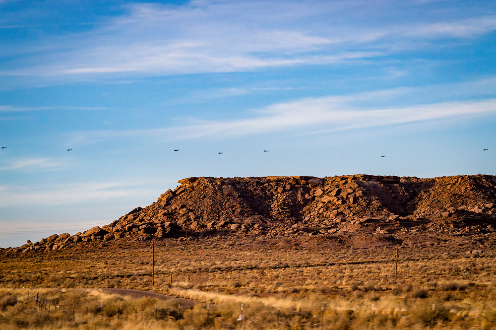 Trail of helicopters flying low over the painted desert in Arizona along Interstate 40.
