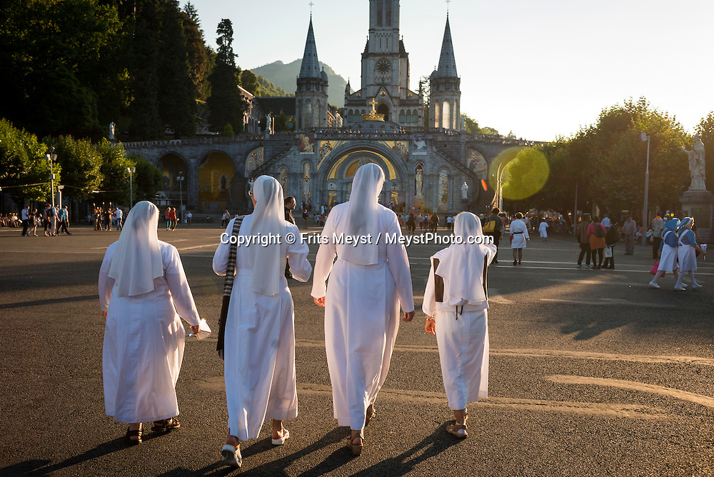 Lourdes, Hautes Pyrenees, France, July 2014. Nuns at the Basilica of the Immaculate Conception.  A pilgrimage is made up of sick and able-bodied pilgrims. The Blessed Virgin Mary is said to have appeared to Bernadette Soubirous on a total of eighteen occasions at Lourdes. Lourdes has become a major place of Roman Catholic pilgrimage and of miraculous healings. Soaring peaks and legendary mountain passes such as the Col du Tourmalet, vast natural corries like the Cirque de Gavarnie and Cirque de Troumouse , valleys dotted with villages with an unspoilt mountain charm, the Marian City of Lourdes and nature reserves protecting the fauna and flora: Hautes Pyrénées is a destination that combines the spectacular and the authentic, a place where pastoral traditions are very much alive. Photo by Frits Meyst / MeystPhoto.com
