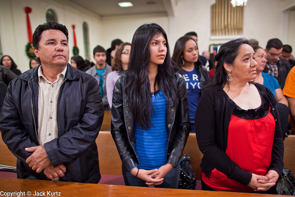 19 DECEMBER 2010 - PHOENIX, AZ: TOMAS AMAYA, left, ELIZABETH HERNANDEZ, and Amaya's wife, CARMEN AMAYA, pray at a prayer service for the DREAM Act in Phoenix. About 100 supporters of the DREAM Act gathered at First Congregational Church of Christ in Phoenix Sunday night, December 19, for a prayer vigil in support of the DREAM Act, which was defeated in the US Senate Saturday, Dec. 18. The DREAM Act, was supported by the Obama administration, and was an important part of the administration's immigration reform platform. The defeat of the DREAM Act, which would have established a path to citizenship for undocumented immigrants who were brought to the US by their parents when they were children, set back the President's immigration reform efforts.    PHOTO BY JACK KURTZ