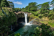 Rainbow Falls or Waianuenue (80 feet tall) glows with a mid morning rainbow in Wailuku River State Park, Hilo, Hawaii, USA.