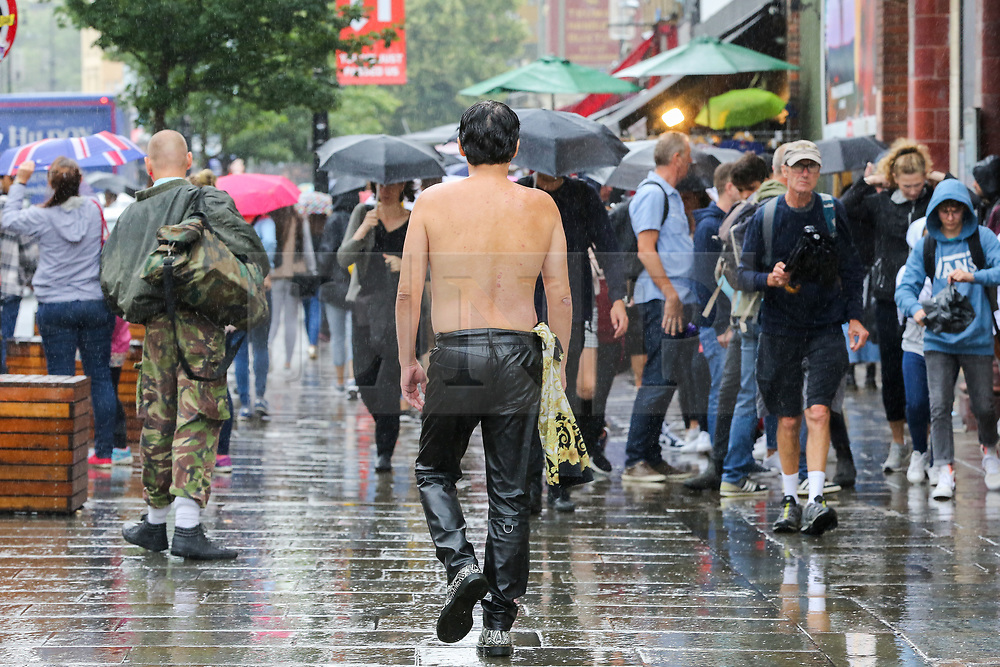 © Licensed to London News Pictures. 30/07/2019. London, UK. A topless man is seen in Camden Market, north London as people shelter from the rain beneath umbrellas during heavy rainfall. Photo credit: Dinendra Haria/LNP