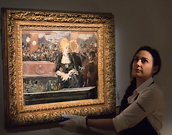 "Sotheby's, London, June 19th 2015. International auctioneers Sotheby's gears up to holding what they say is London's highest valued auction of contemporary artworks, to be held on June 24th 2015 where the combined artworks are anticipated to bring in as much as £203 million. PICTURED: A Sotheby's gallery technician adjust the hanging of Edourd Manet's famous ""Le bar aux Folies-Bergere"", the first version of his celebrated oil on canvas which is now in the collection of the Courauld Gallery. Painted in 1881, it is expected to fetch between £15-20 million at auction.   // Payment/Licencing/Contact details: Paul@pauldaveycreative.co.uk Tel: 07966016296"
