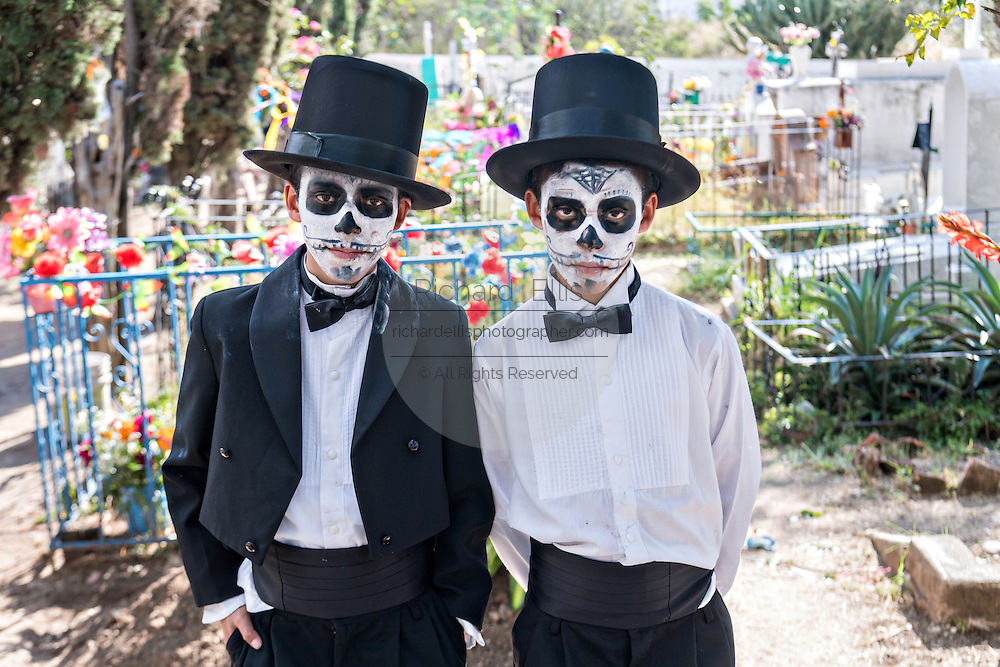 Children dresses as dapper skeletons in the Nuestra Senora de Guadalupe cemetery  during the Day of the Dead festival November 1, 2016 in San Miguel de Allende, Guanajuato, Mexico. The week-long celebration is a time when Mexicans welcome the dead back to earth for a visit and celebrate life.