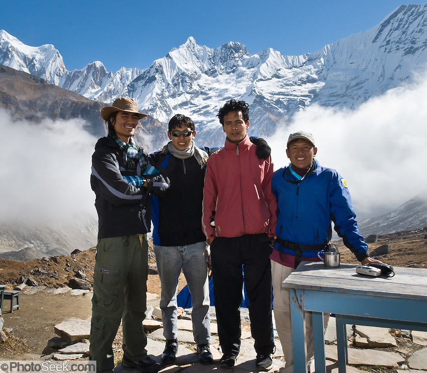 Our porters and guides stand beneath the sharp peak of Gandharba Chuli (20,500 feet / 6248 meters), with fluted ice ridges, in the Annapurna Range of Nepal, seen from the Annapurna Sanctuary.