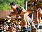 22 JULY 2016 - TENGANAN DUAH TUKAD, BALI, INDONESIA:  Men engage in pandanus fights in the Tenganan Duah Tukad village on Bali. The ritual Pandanus fights are dedicated to Hindu Lord Indra. Men engage in ritual combat with spiky pandanus leaves and rattan shields. They usually end up leaving bloody scratches on the combatants' backs. The young girls from the community wear their best outfits to watch the fights. The fights have been traced to traditional Balinese beliefs from the 14th century CE. The fights are annual events in the Balinese year, which is 210 days long, or about every seven months in the Gregorian calendar.   PHOTO BY JACK KURTZ
