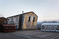 """SOVERIA MANNELLI, ITALY - 17 NOVEMBER 2016: """"The Falling House"""", an installation by artist Fabrizio Plessi, is seen here in the main square Piazza Bonini in Soveria Mannelli, Italy, on November 17th 2016.<br /> <br /> Soveria Mannelli is a mountain-top village in the southern region of Calabria that counts 3,070 inhabitants. The town was a strategic outpost until the 1970s, when the main artery road from Naples area to Italy's south-western tip, Reggio Calabria went through the town. But once the government started building a motorway miles away, it was cut out from the fastest communications and from the most ambitious plans to develop Italy's South. Instead of despairing, residents benefited of the geographical disadvantage to keep away the mafia infiltrations, and started creating solid businesses thanks to its administrative stability, its forward-thinking mayors and a vibrant entrepreneurship numbering a national, medium-sized publishing house, a leading school furniture manufacturer and an ancient woolen mill."""