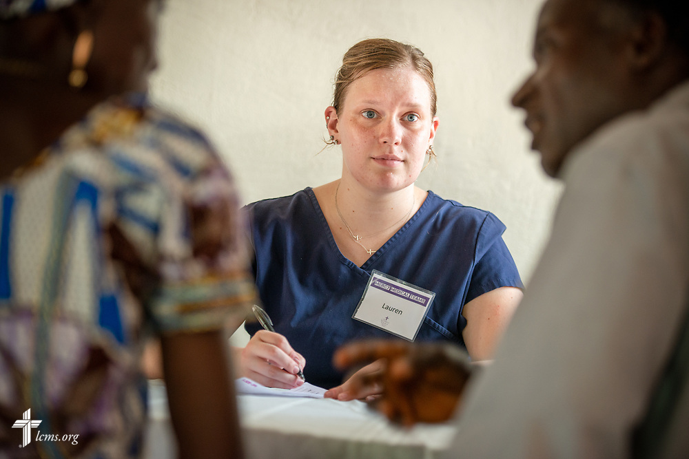 Lauren Awe, a nurse attending Beautiful Savior Lutheran Church, La Vista, Neb., listens to a patient on the second day of the LCMS Mercy Medical Team on Tuesday, May 8, 2018, in the Yardu village outside Koidu, Sierra Leone, West Africa. LCMS Communications/Erik M. Lunsford