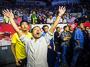 27 JULY 2015 - BANGKOK, THAILAND:  Spectators react to their fighter's status during a bout at Rajadamnern Boxing Stadium (also spelled Ratchadamnoen Stadium). It is Bangkok's oldest venue for Muay Thai. It hosts bouts on Monday, Wednesday, Thursday and Sunday. Ringside seats are about 2,000 Thai Baht (approximately $57 US). The stadium hosted its first fight in December, 1945.        PHOTO BY JACK KURTZ