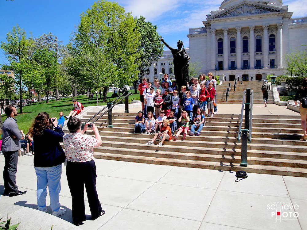 A class of school children get their picture taken outside of Wisconsin's State Capitol.