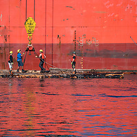 Lumberjacks attaching logs to a crane on the water next to an orange ship in the Nanaimo harbor in British Columbia, Canada.