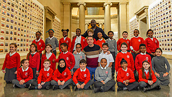 "© Licensed to London News Pictures. 11/11/2019. LONDON, UK. Turner Prize-winning artist and Oscar-winning filmmaker Steve McQueen poses with staff and pupils from Tyssen Community School from Hackney at the preview of ""Year 3"", his new exhibition at Tate Britain.  The artwork comprises 3,128 traditional school class photographs of Year 3 pupils from 1,504 of London's primary schools.  The work reflects a picture of the present and is on display 12 November to 3 May 2020.  Photo credit: Stephen Chung/LNP"