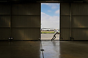Jay, a pilot with AIM Air, opens the hanger doors before a flight to Arua, South Sudan.