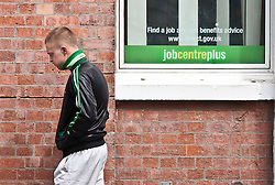 FILE PICTURE © licensed to London News Pictures. LONDON, UK UK unemployment figures released today FILE PICTURE 12/10/11. A young man waits in front of a Jobcentre Plus as the unployment level reaches the highest level of 17 years in the UK. Photo credit should read TOLGA AKMEN/LNP
