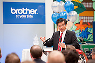 Male in suit giving a spoken presentation for brother into a microphone to a crowd