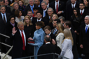President Donald Trump takes the oath of office from Chief Justice John Roberts as his wife Melania, holds two Bibles, a personal family Bible and the Bible that President Lincoln used at his first inauguration and surrounded by his five children January 20, 2017 in Washington, DC. Trump became the 45th President of the United States.
