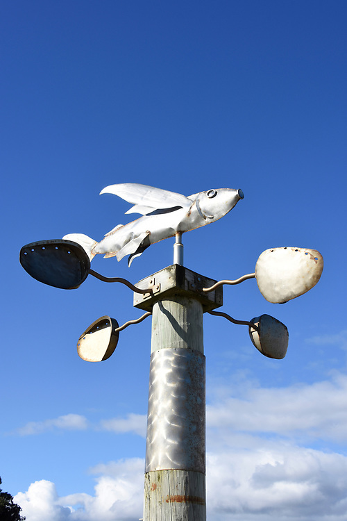 Fish style weather vane against a blue sky with clouds