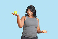 Overweight mixed race woman holding green apple and donut over blue background