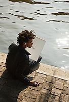A young woman sketches on the banks of the Seine, Paris, France.