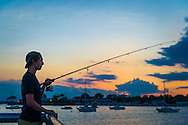 Port Washington, New York, USA. 26th June 2015.  A young man, wearing cap backwards, is fishing as sunset approaches, on the Town Dock on the shores of Manhasset Bay in the North Shore village on Long Island Gold Coast.