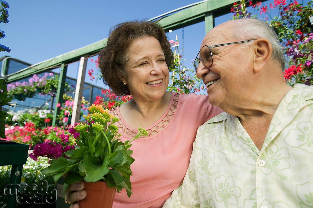 Senior Couple sitting among flowers at plant nursery close up